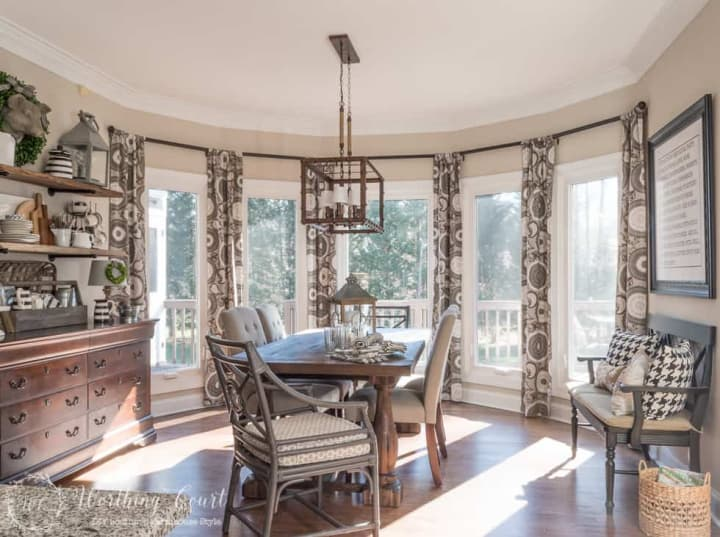 draperies and dining table in a large bay window