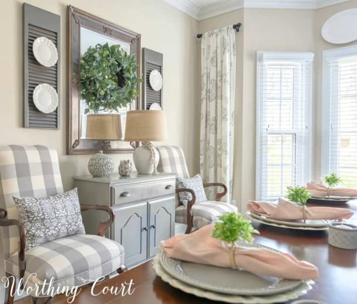buffalo check chairs flanking gray chest with mirror above
