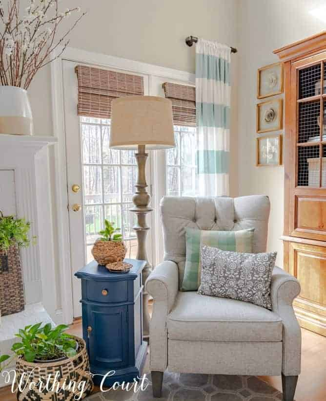 gray recliner in front of French doors with blue and white draperies