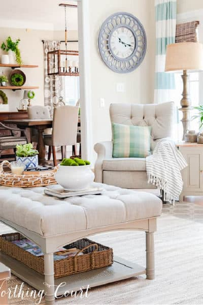 upholstered ottoman, gray tufted back recliner and blue and white curtains in the corner of a family room