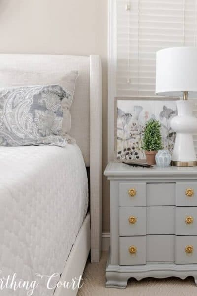 light gray nightstand with a white lamp