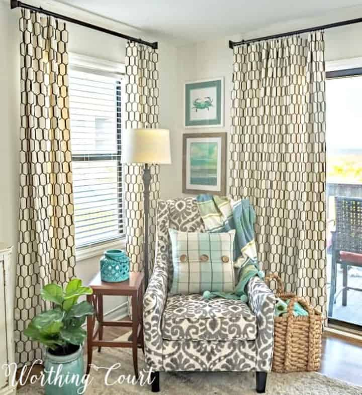 pair of draperies on windows in a corner with a chair in front