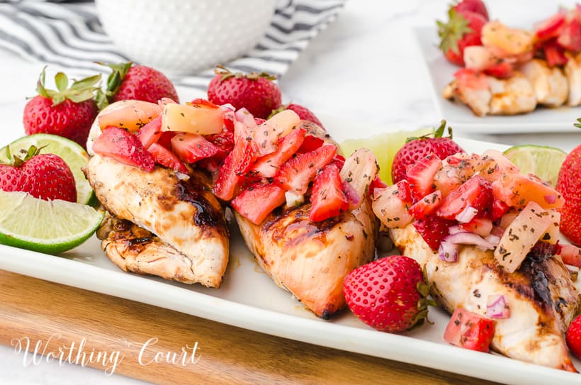 platter of sliced grilled chicken breast topped with strawberry and pineapple salsa