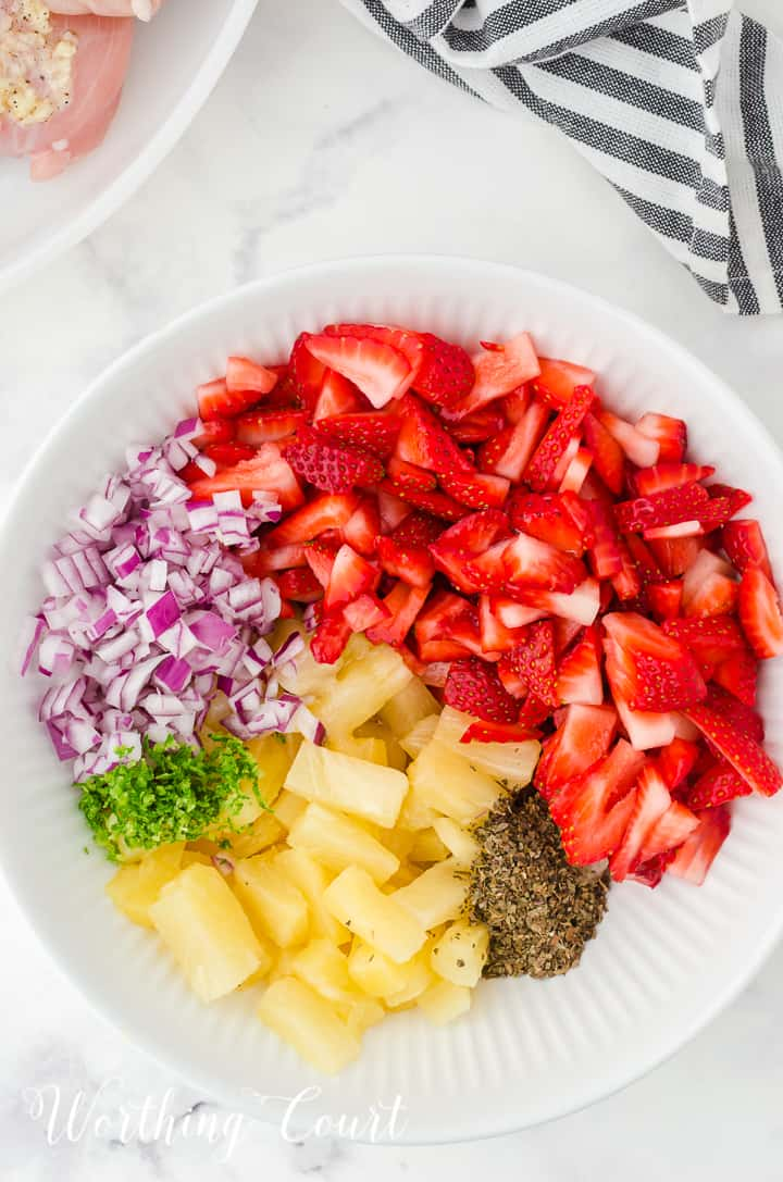 ingredients for strawberry and pineapple salsa in a white bowl