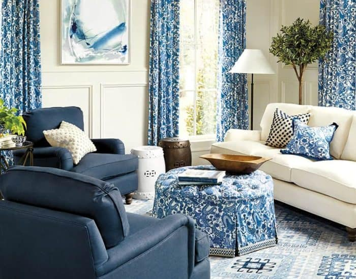 living room with blue and white furniture, rug, draperies and accessories
