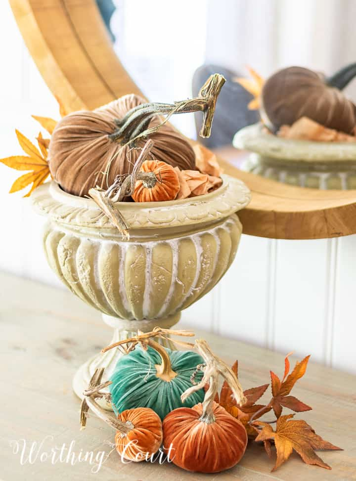 various colored velvet pumpkins and fall leaves in an urn and on the table surface