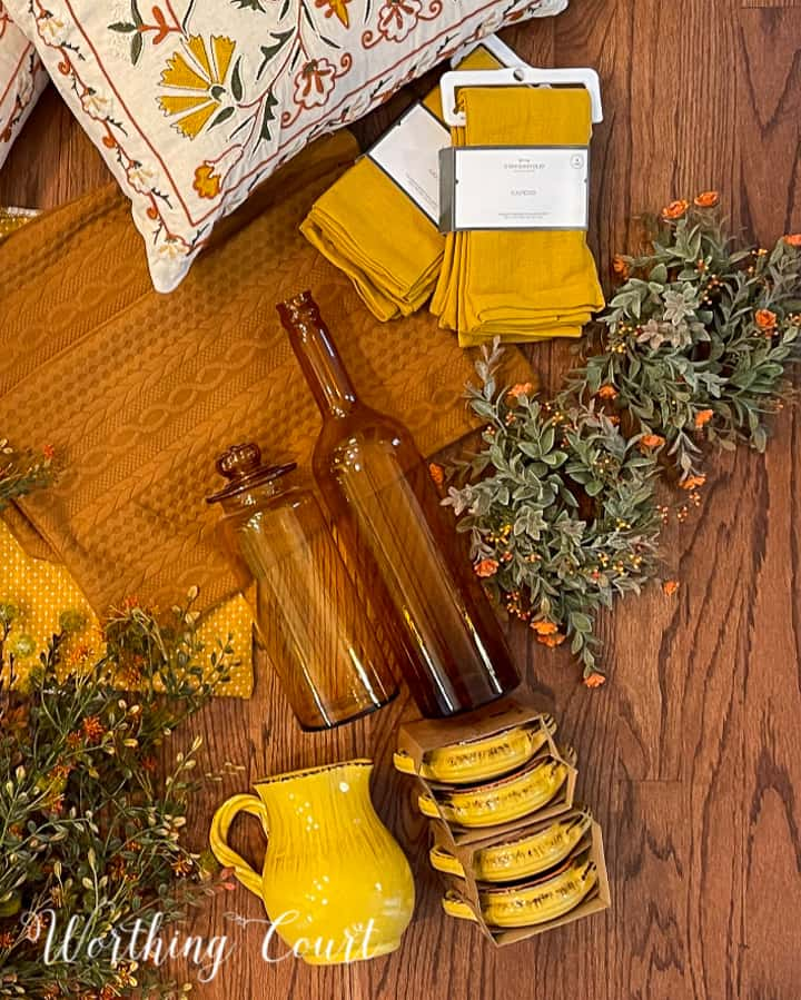 overhead view of amber jars, yellow napkins, fall foliage and yellow dishes laying on a hardwood floor