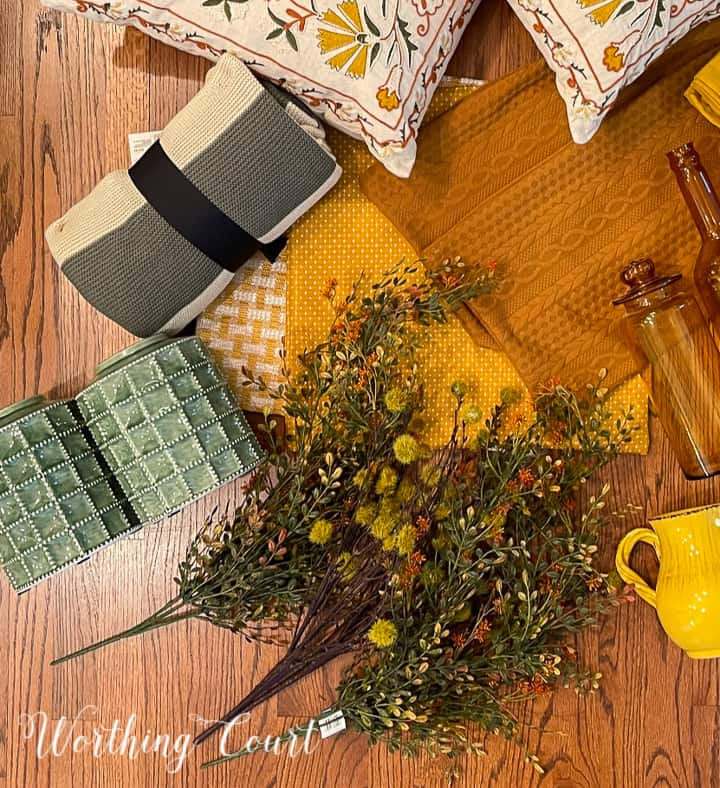 overhead view of pair of green urns, fall foliage, striped throw and yellow pillow covers on a hardwood floor