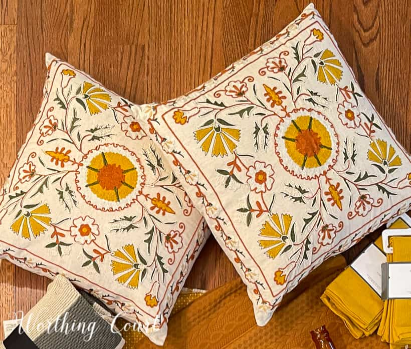 pair of pillows embroidered with yellow, green and deep orange on a cream background
