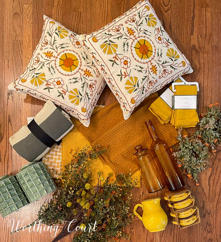 overhead view of fall decorations on a hardwood floor including pillows, foliage, dishes, pillow covers and a throw