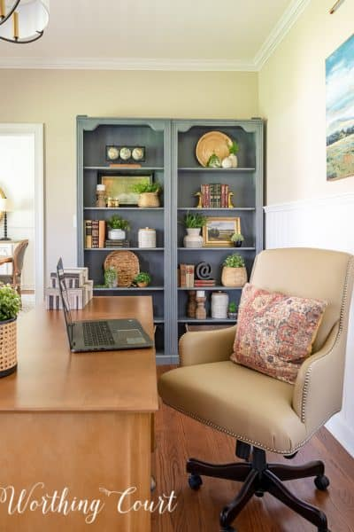 pair of gray bookcases filled with a variety of updated traditional accessories with a beige leather office chair in the foreground