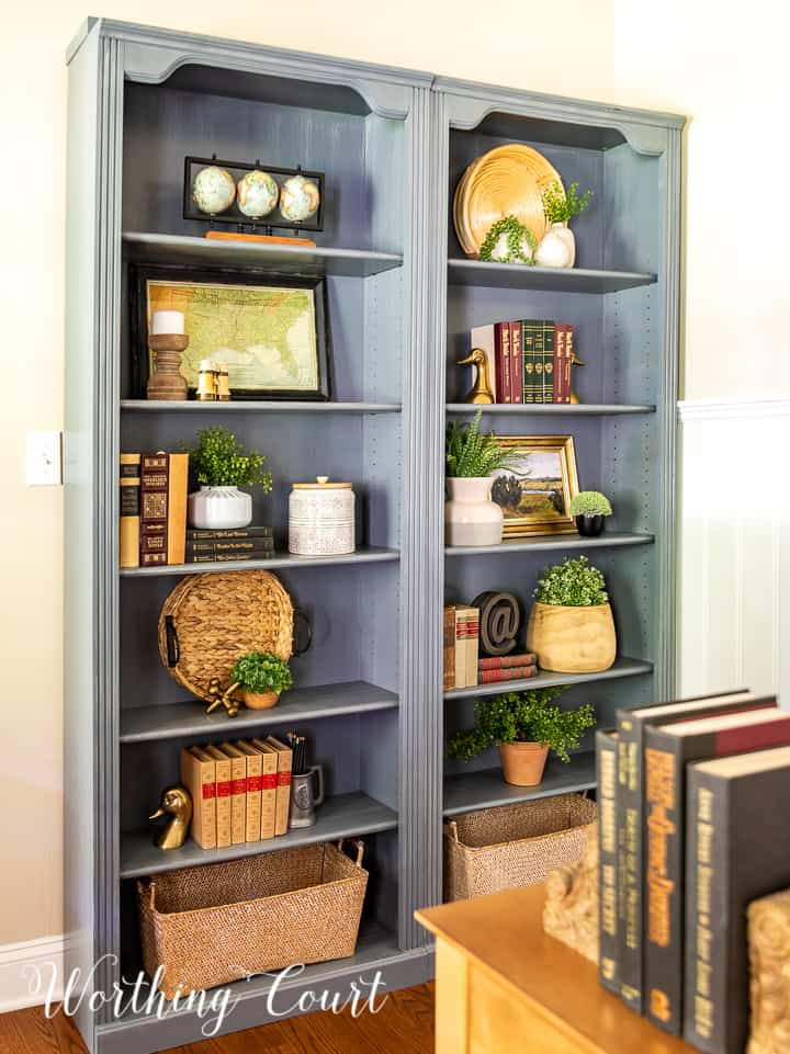 pair of gray bookcases filled with a variety of updated traditional accessories