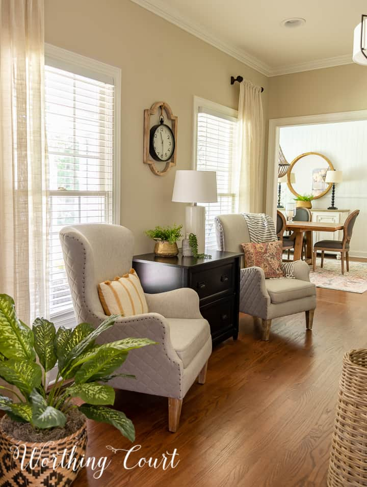 pair of club chairs in a home office with a view into the dining room