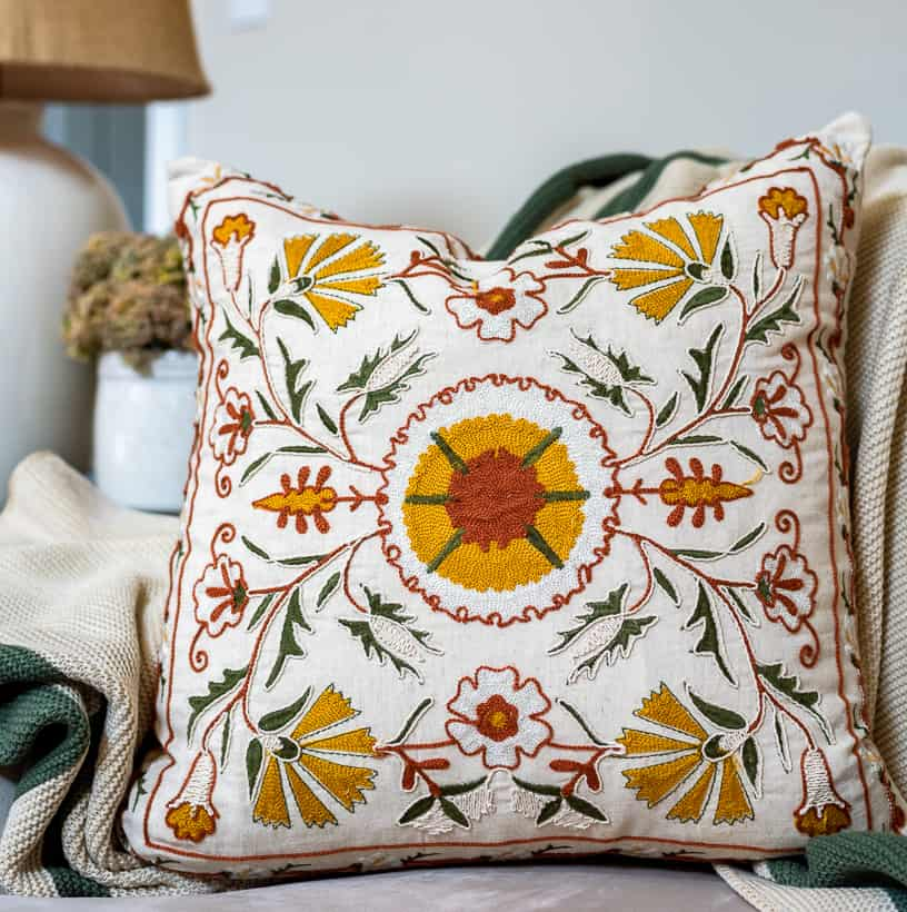 embroidered pillow with yellow, green and deep orange on a cream background
