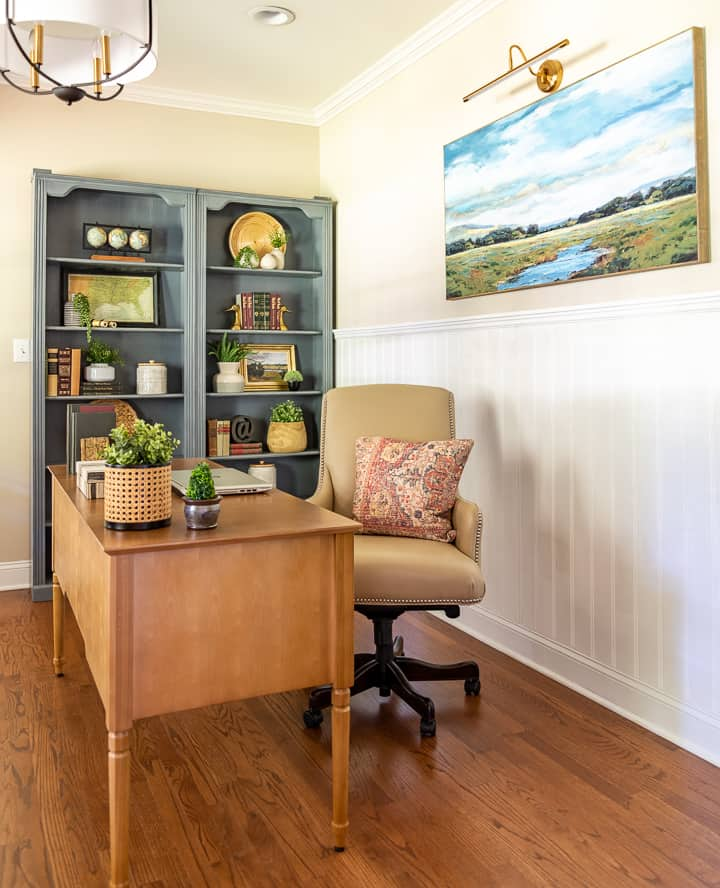 natural wood desk with beige leather chair and gray bookcases filled with accessories in background