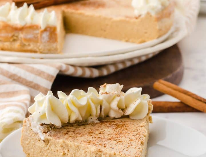 image of one piece of gingerbread cheesecake on a plate with rest of cheesecake in the background