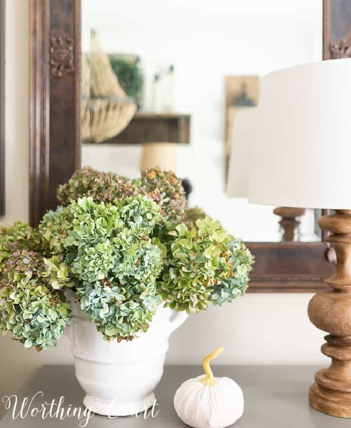 blue dried hydrangeas in a white urn on a gray chest in front of a mirror with a lamp and small white pumpkin