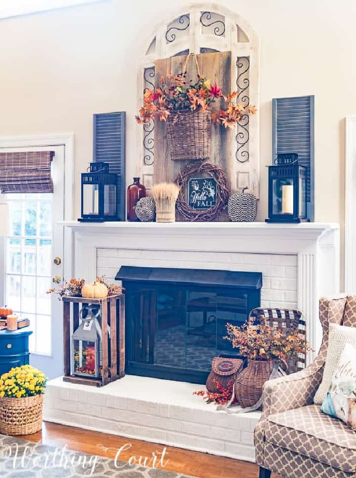 white fireplace overflowing with an abundance of fall decorations