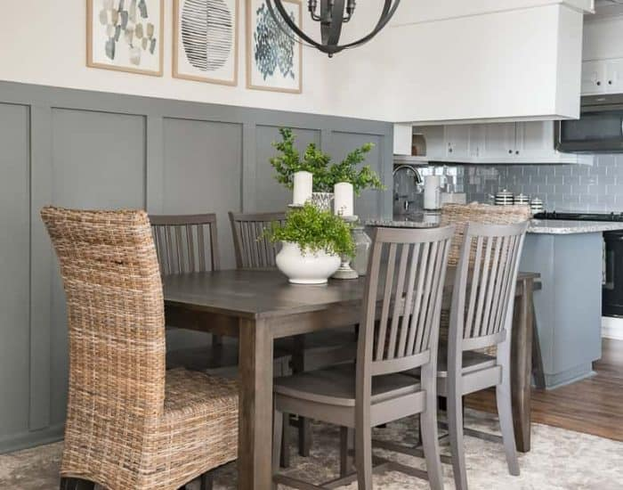 dining room with gray board and batten wall, dining table and six chairs and a modern orb chandelier