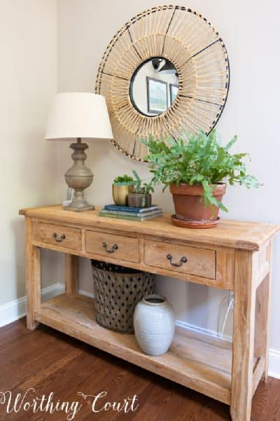 wood console table topped with a lamp, accessories and a plant and a round mirror on the wall above