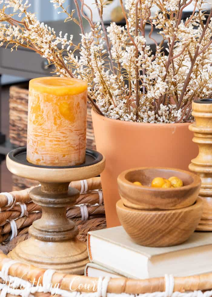 fall vignette in a basket tray with wood accents, terra cotta pot, candle and dried stems