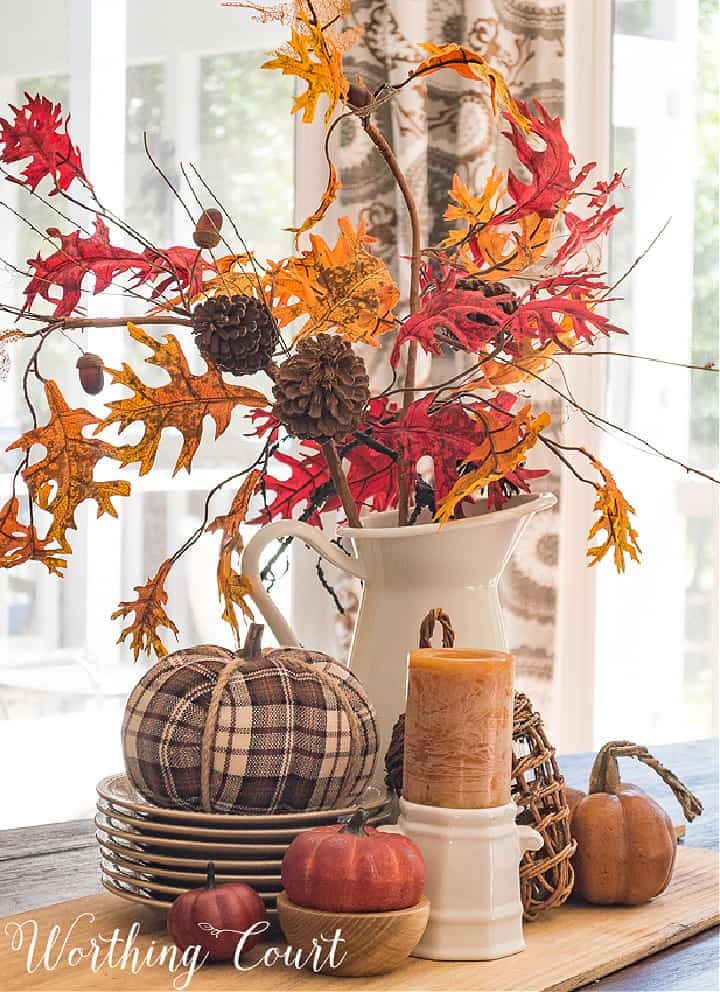 fall centerpiece on a wood board with fall leaves in a white pitcher and a plaid pumpkin on a stack of gray plates