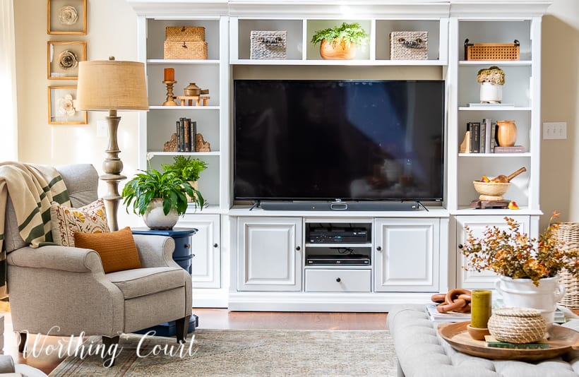 white entertainment center filled with tv and fall decor with a gray chair and coffee table in front