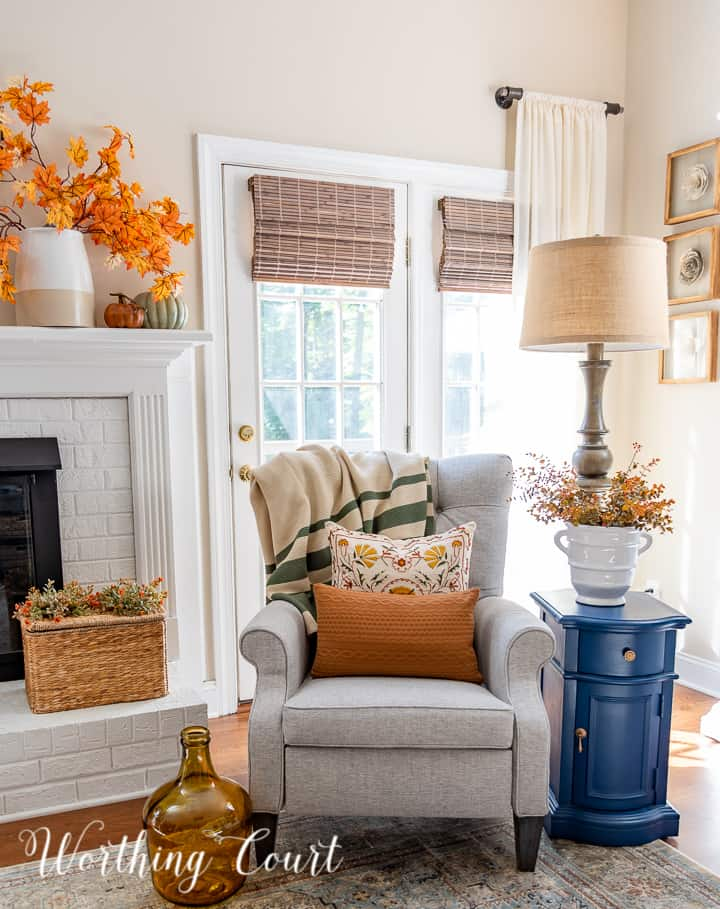 gray chair in front of windows beside white fireplace with fall decor