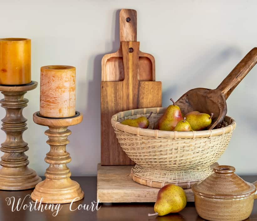 woven pedestal bowl filled with faux pears in front of cutting boards