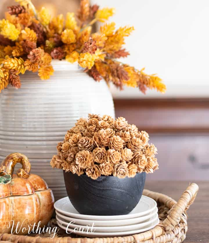 fall centerpiece in a woven tray with a containers filled with faux fall stems and a ceramic pumpkin box
