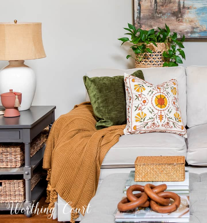 fall pillows and throw blanket on a neutral colored couch