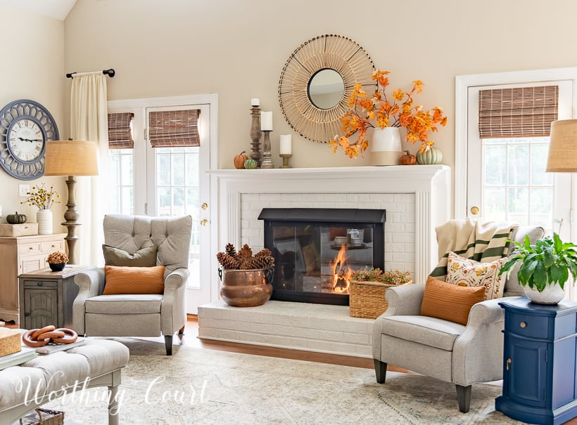 gray arm chairs, lamps and side tables beside white fireplace with fall decor on the mantel and hearth
