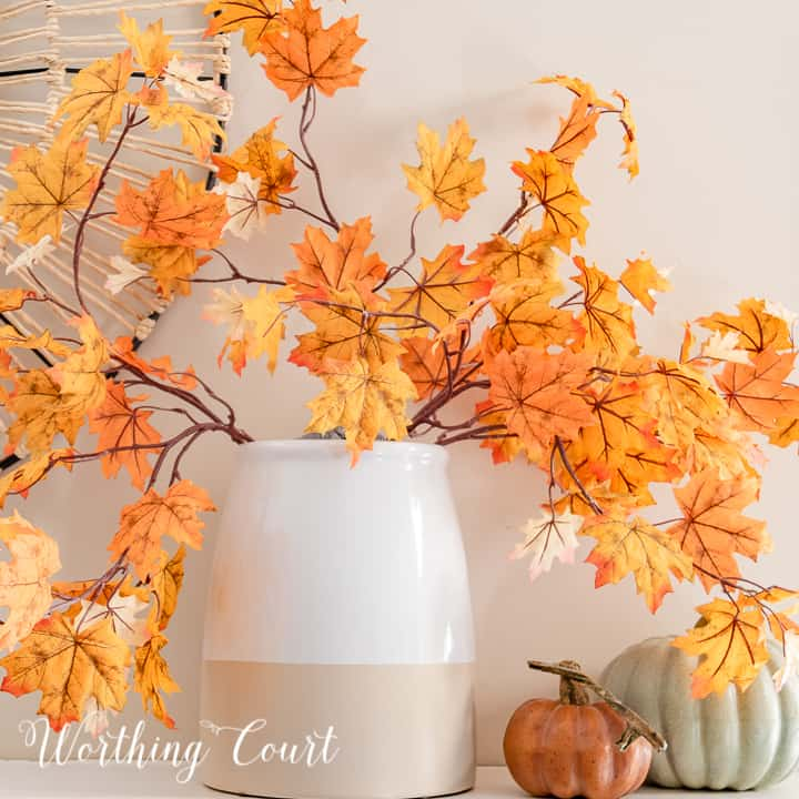 vase with fall leaf stems and two faux pumpkins on a white mantel