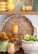 fall vignette on a sideboard with amber, gold and green accessories