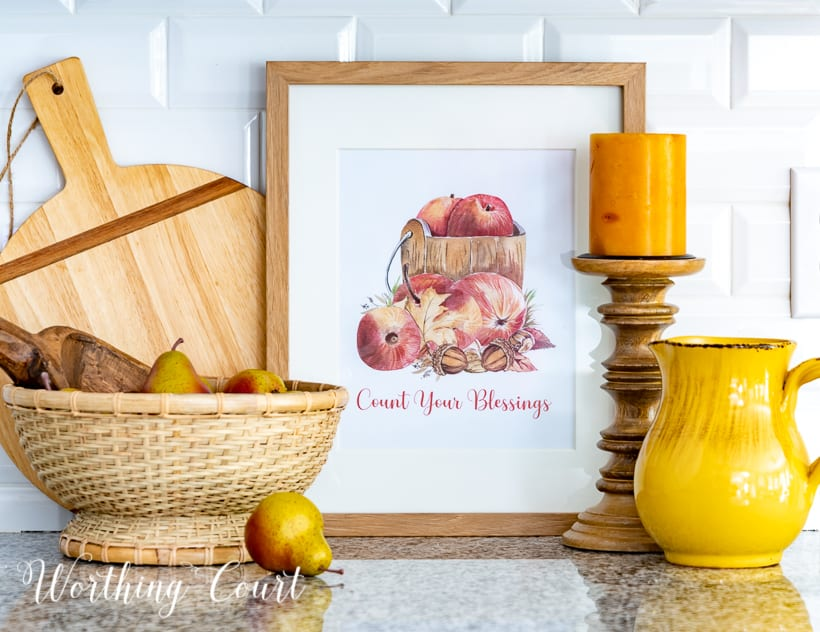 Graphic image of apples in a wood bucket with count your blessings wording below
