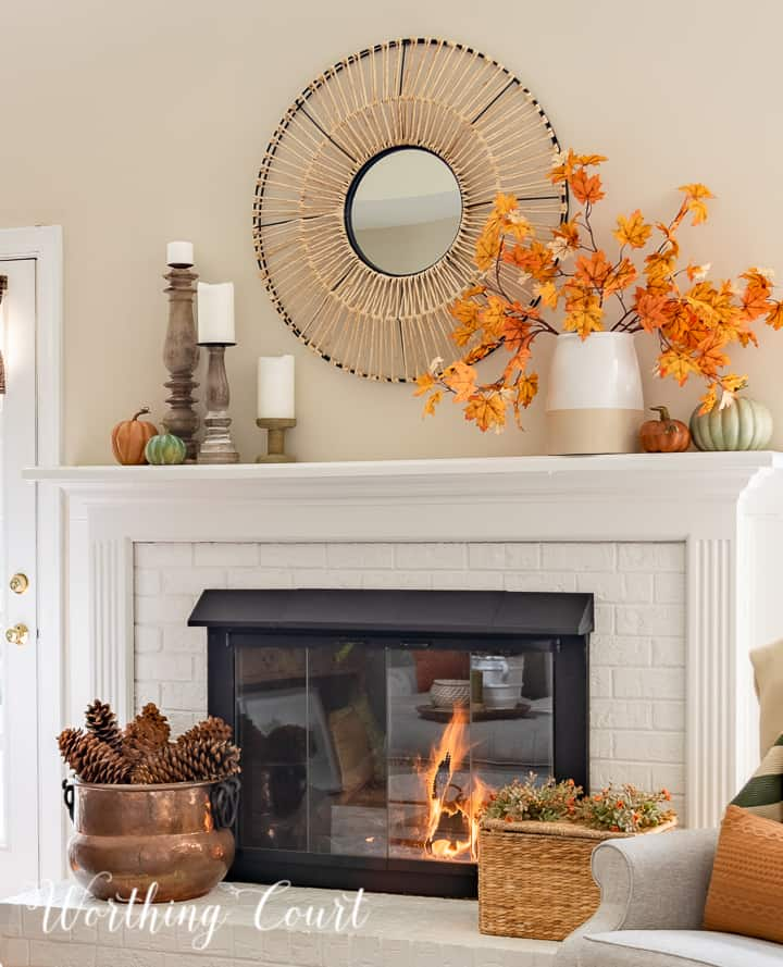 white mantel with round mirror above and fall decorations