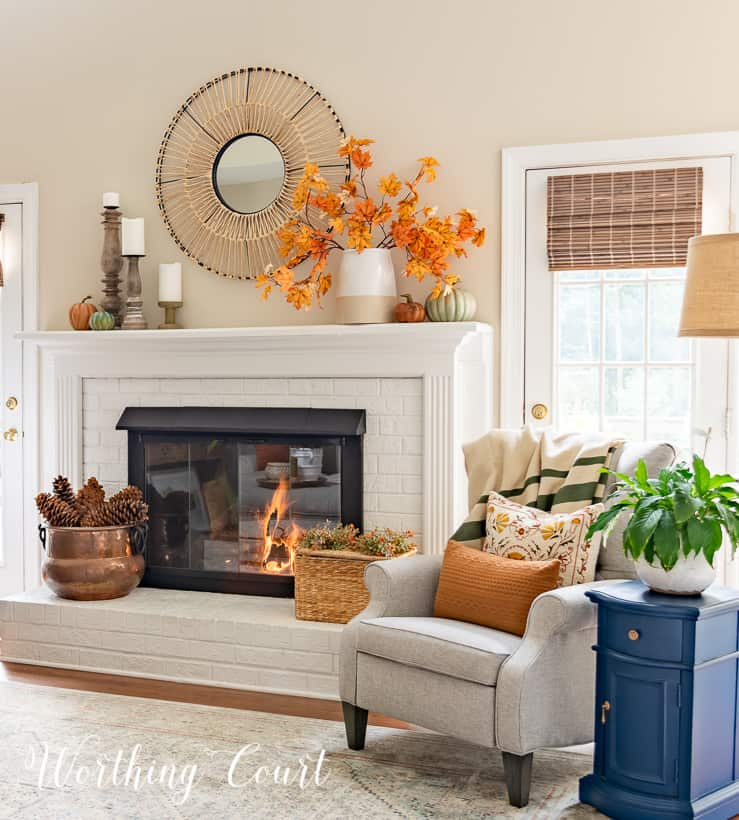gray arm chair and side table beside white fireplace with fall decor on the mantel and hearth