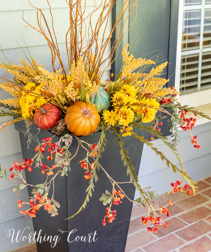 natural sticks, faux golden mums and multi colored pumpkins in a tall black urn