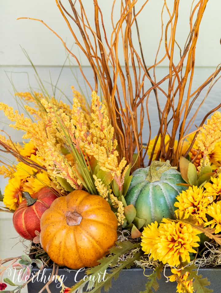 natural sticks, faux golden mums and multi colored pumpkins in the top of an urn