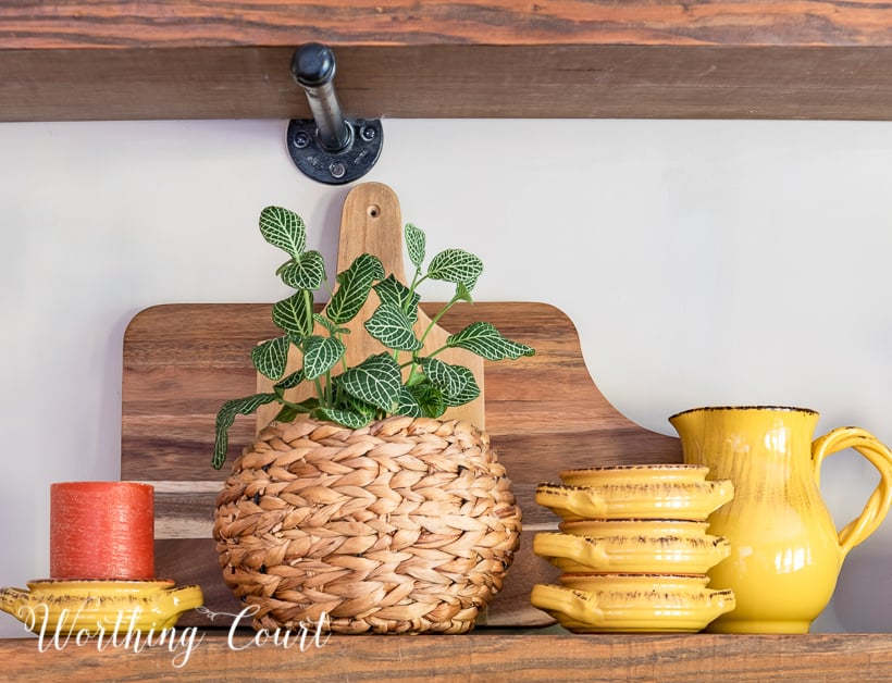 wooden open shelves decorated for fall with rich amber and green accessories