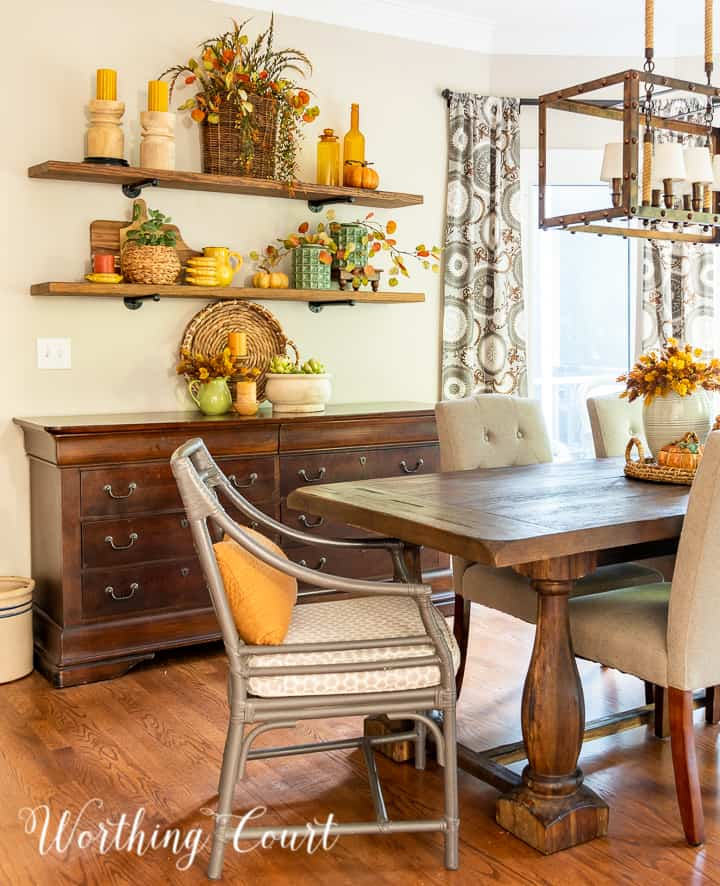 dining area with open shelves above a sideboard decorated for fall