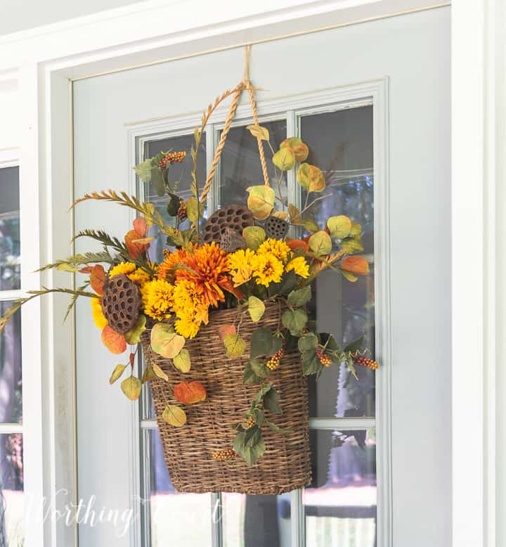 handing basket on gray front door filled with fall colored faux stems