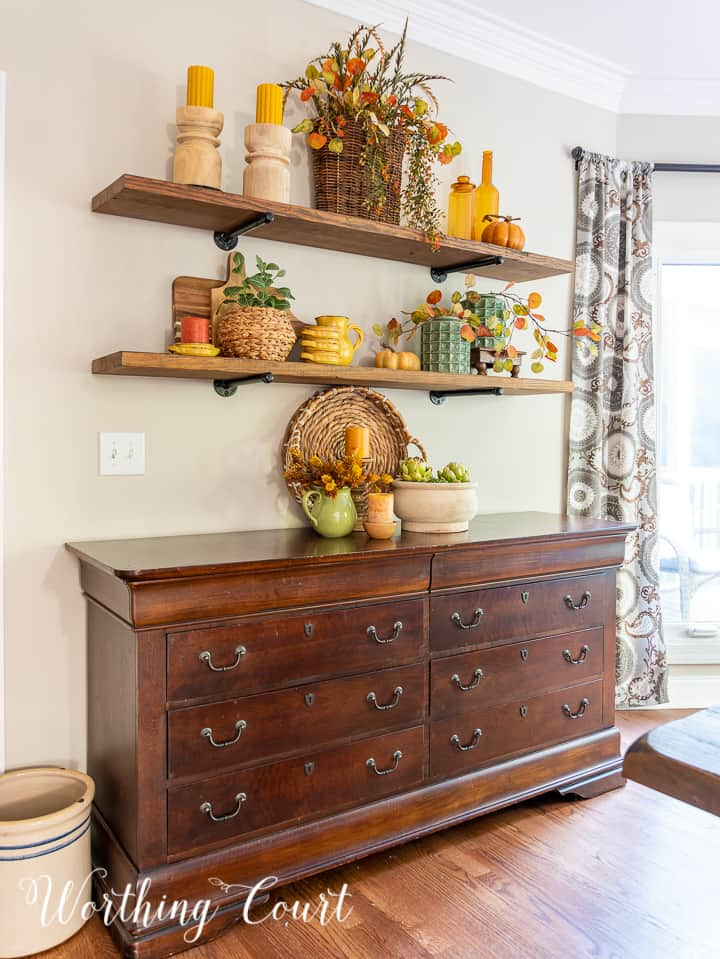 wooden open shelves above a sideboard decorated for fall with rich amber and green accessories