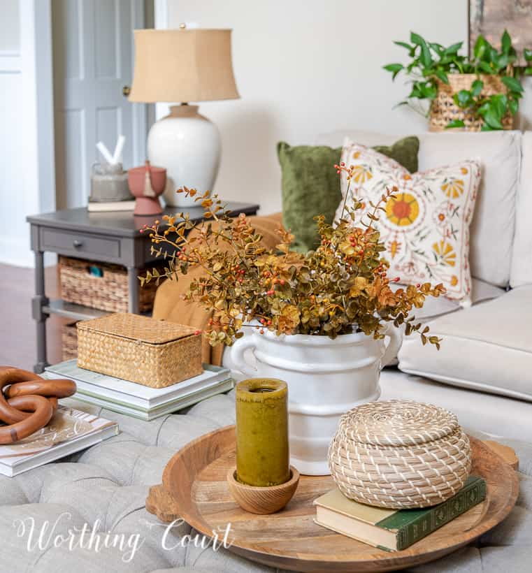 fall vignette on upholstered coffee table in front of neutral covered couch with fall pillows
