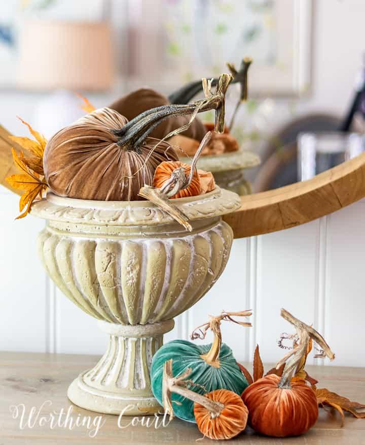 pedestal bowl filled with multiple velvet pumpkins in different colors