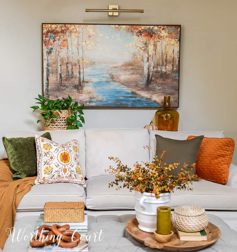 neutral colored couch filled with fall pillows with an upholstered coffee table in front
