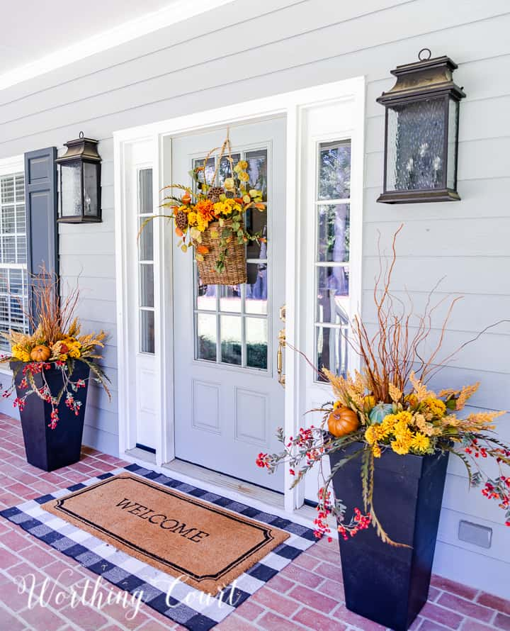 gray front door with a hanging basket and flanked with urns filled with faux fall stems and pumpkins in fall colors
