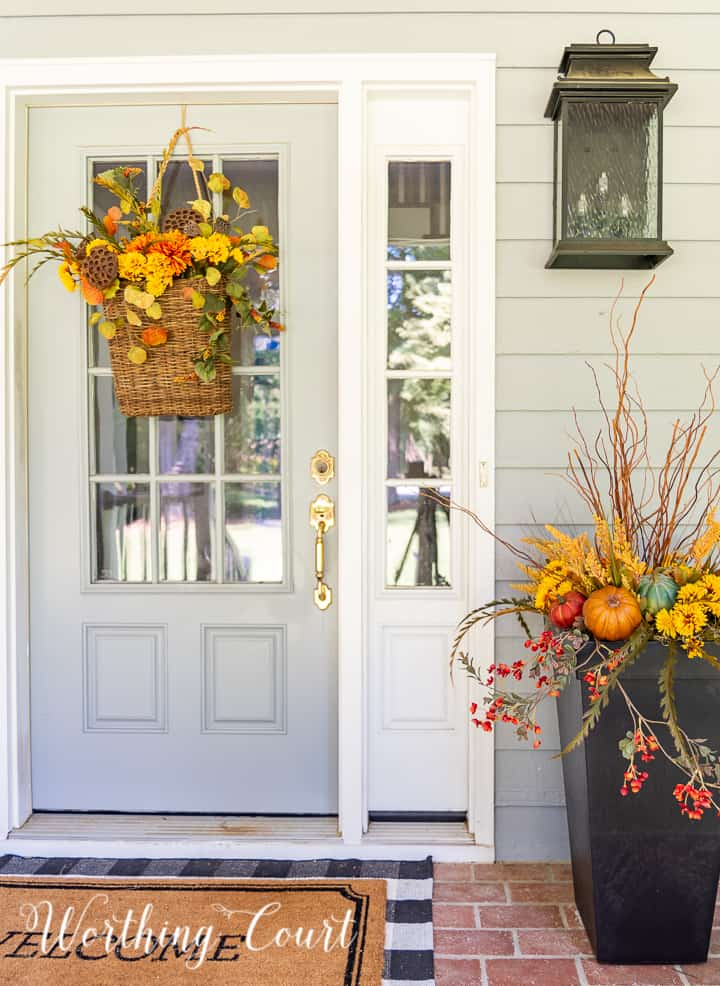 gray front door with a hanging basket and urn filled with faux fall stems and pumpkins in fall colors