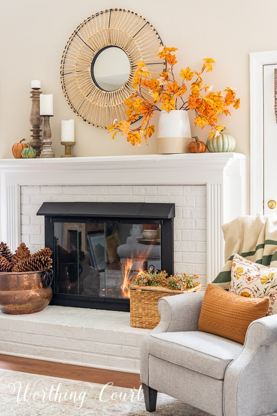 white fireplace with fall decor on the mantel and hearth