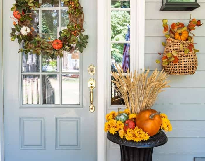 urn with fall decor beside gray front door with a fall wreath